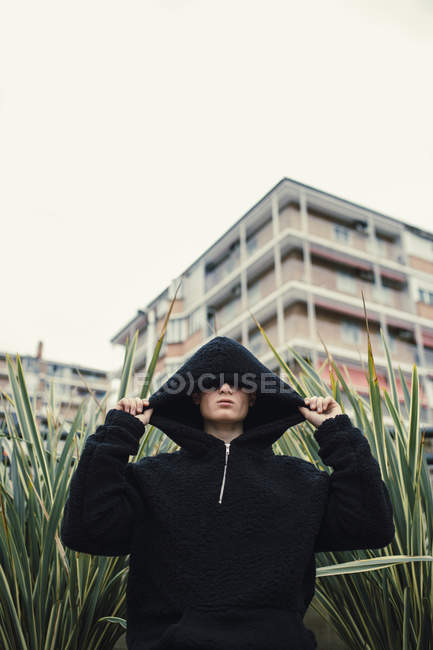 Man wearing black hooded jacket standing in green bush in city — Stock Photo