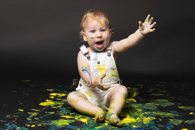 Adorable dirty little boy sitting and playing with yellow and blue paint on dark background. — Stock Photo