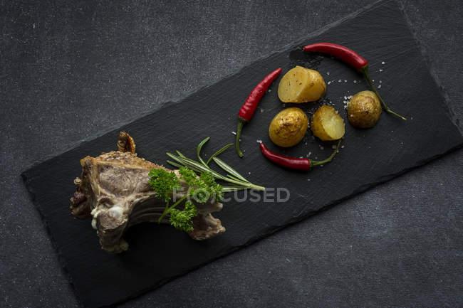 Assado de cordeiro com batatas na ardósia guarnecido com salsa e pimenta — Fotografia de Stock