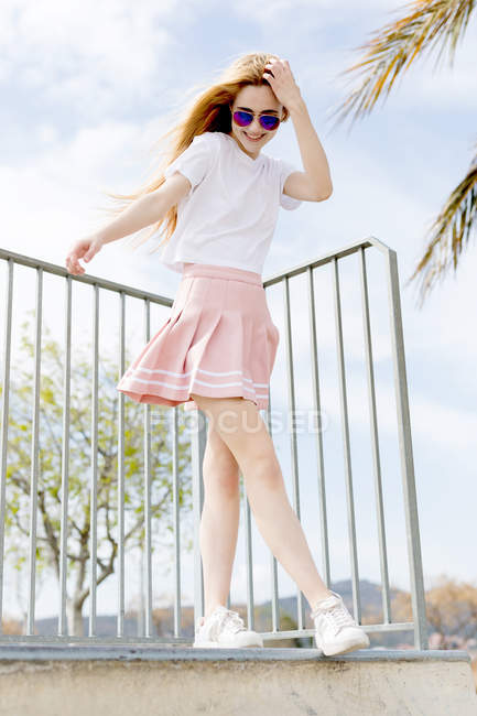 Trendy blonde girl with long hair in sunglasses standing in short pink skirt and smiling — Stock Photo