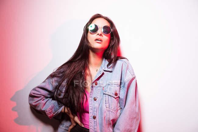 Pretty young pink dressed woman in sunglasses standing at white wall — Stock Photo