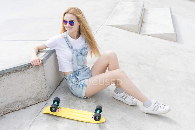 Blonde girl sitting sitting on asphalt with penny board — Stock Photo