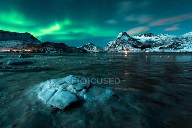 Трещины в слое льда на воде с горами под северным сиянием ночью — стоковое фото