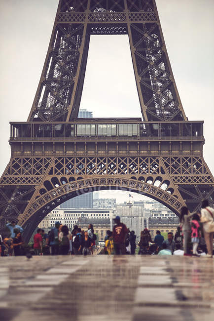 Basement of Eiffel Tower crowded by tourists on background of cityscape, Paris, France — стоковое фото
