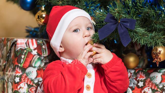 Маленький хлопчик в костюмі Діда Мороза сидять на ялинку і кусає м'яч — стокове фото