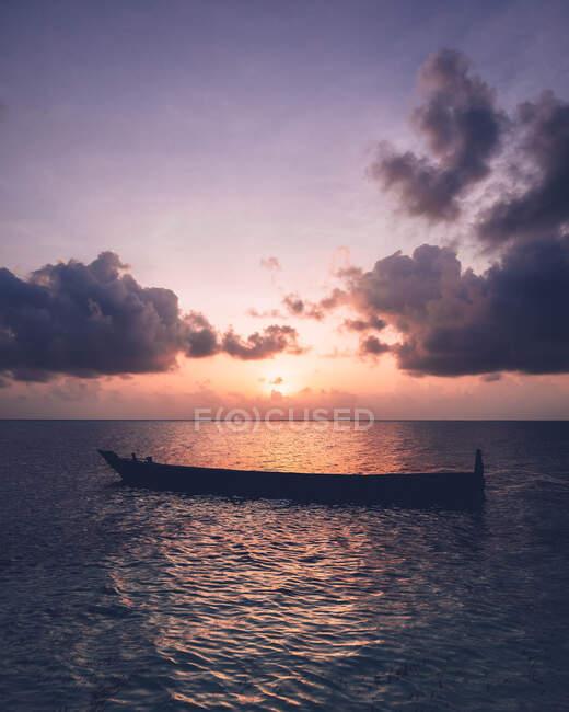 Bateau vide flottant dans l'océan sous le ciel nuageux et le coucher du soleil. — Photo de stock