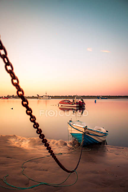 Moored boat on chain in shallow water of tranquil harbor in sunset light, Spain — Stock Photo