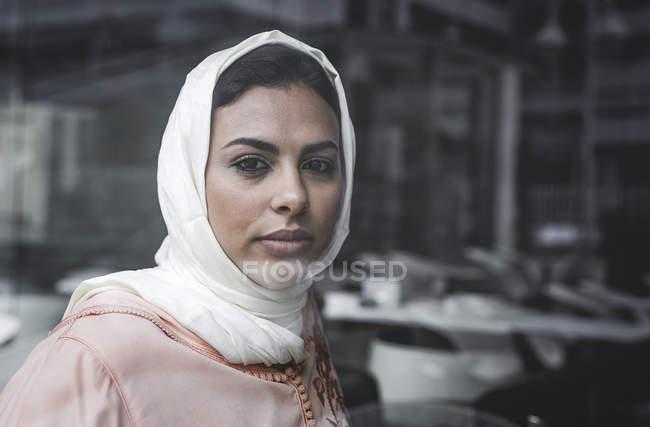 Портрет вдумливі Марокканський жінка з хіджаб сидить позаду області вікна — стокове фото