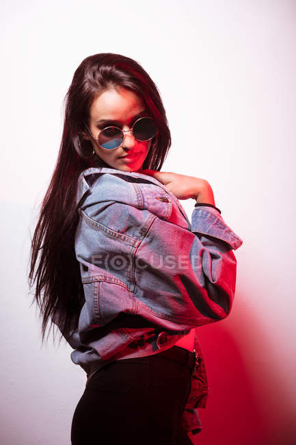 Pretty young pink dressed woman in sunglasses standing at white wall and looking at camera — Stock Photo