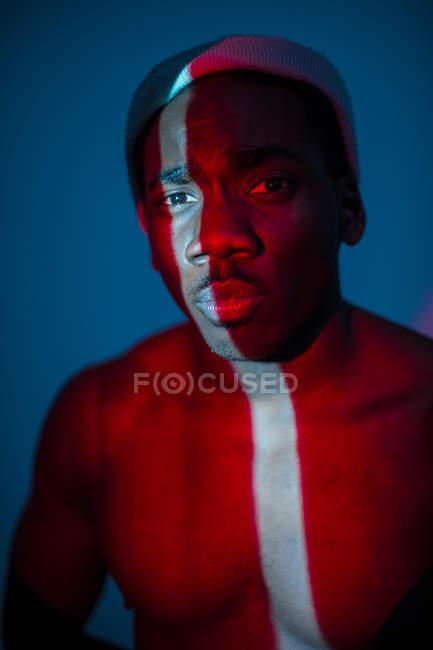 Безэмоциональный этнический мужчина, стоящий со световой линией на теле и смотрящий в камеру — стоковое фото