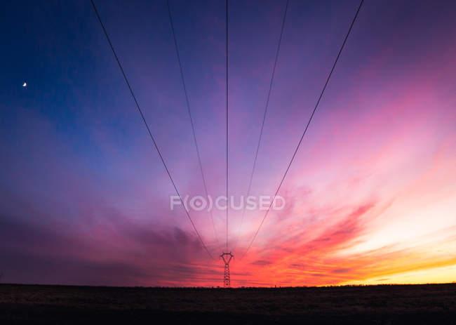 Cables de alimentación bajo el increíble cielo multicolor - foto de stock