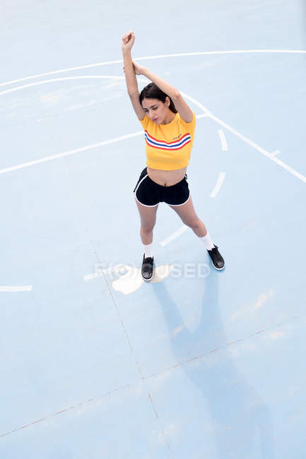 Slim young woman in sportswear standing on blue sports ground — Stock Photo
