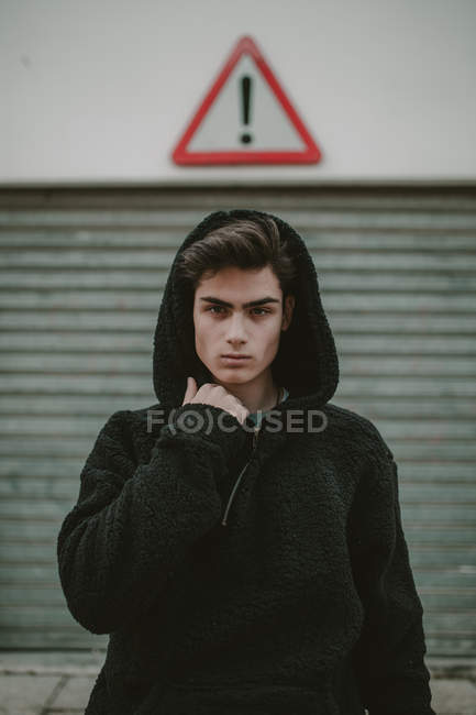 Thoughtful teenager in black hooded jacket standing on street with exclamation sign and looking at camera — Photo de stock