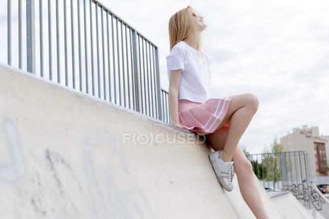 Stylish blonde girl in sunglasses sitting in skate park — Stock Photo