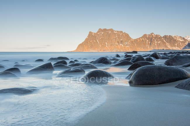 Pietre scure lisce in lungo flusso di esposizione di acqua sullo sfondo di scogliere, Lofoten, Norvegia — Foto stock
