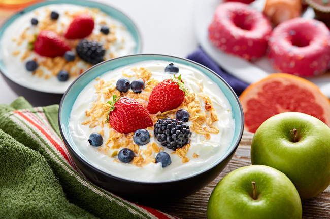 Breakfast bowl of yogurt and berries on table with ingredients — Stock Photo