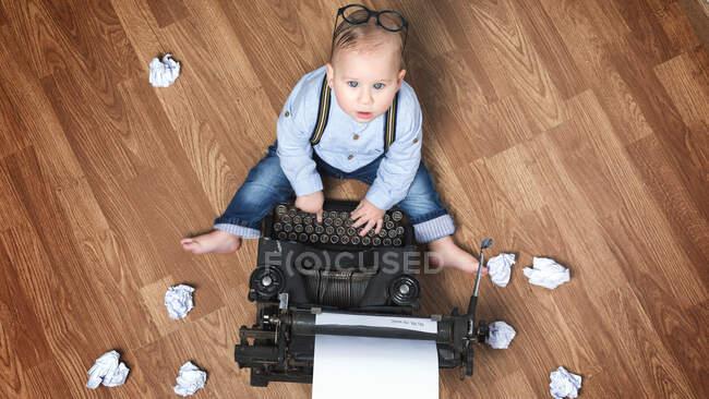 Dall'alto adorabile bambino seduto alla macchina da scrivere con fogli di carta sul pavimento. — Foto stock