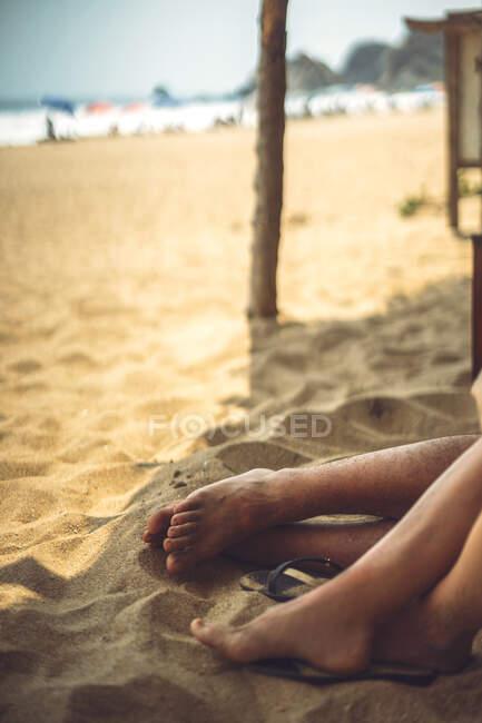 Gambe ritagliate di giovane coppia sdraiata sulla sabbia mentre riposava su una bella spiaggia — Foto stock