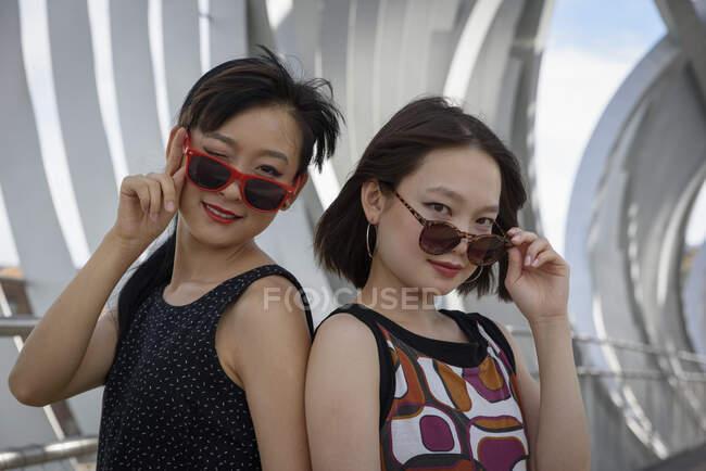 Duas mulheres asiáticas atraentes em óculos de sol sorrindo e olhando para a câmera enquanto estava no fundo da estrutura moderna no parque — Fotografia de Stock