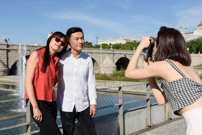 Жінка фотографує азіатську пару. — стокове фото