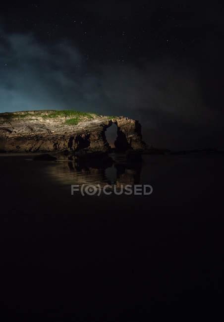Acantilado arqueado situado cerca del mar tranquilo por la noche en la naturaleza, Asturias, España - foto de stock