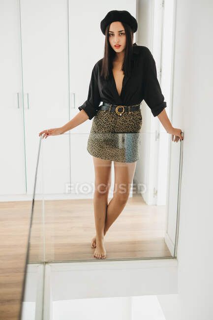 Lovely young lady in stylish outfit and beret smiling and looking up while leaning on glass railing at home — Stock Photo