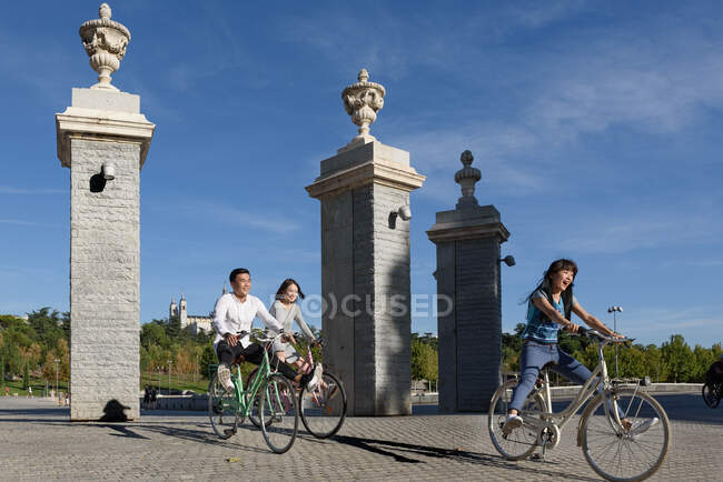 Cheerful Asian people riding bicycles in park — Stock Photo
