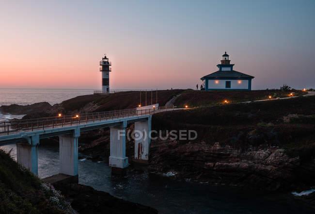 Pont lumineux moderne situé près d'un petit îlot avec balise et maison au crépuscule, Asturies, Espagne — Photo de stock