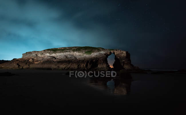 Arched cliff located near calm sea at night in nature, Asturias, Spain — Stock Photo