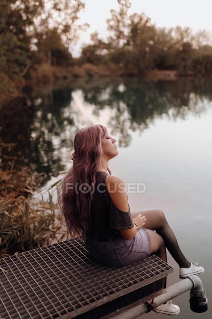 Vue latérale de la femme sensuelle avec les cheveux roses assis sur la jetée au-dessus du lac dans la paix — Photo de stock