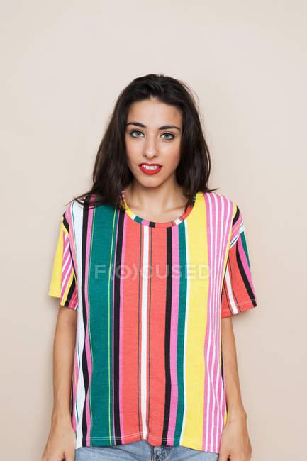 Ritratto di giovane donna sicura di sé in camicia a righe colorate — Foto stock