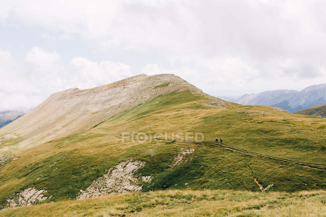 Traveler walking along green mountain ridge in nature — Stock Photo