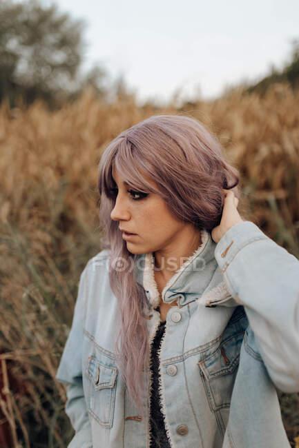 Vista lateral da bela mulher moderna com cabelo rosa fumar cigarro com os olhos fechados na natureza outonal — Fotografia de Stock