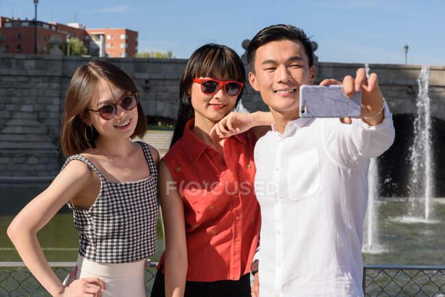 Asian tourists taking selfie near fountain — Stock Photo