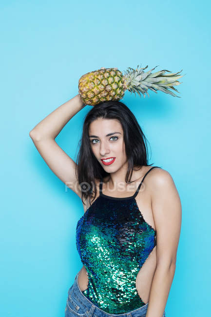 Young woman posing in glitter festive top posing with pineapple on blue background — Stock Photo