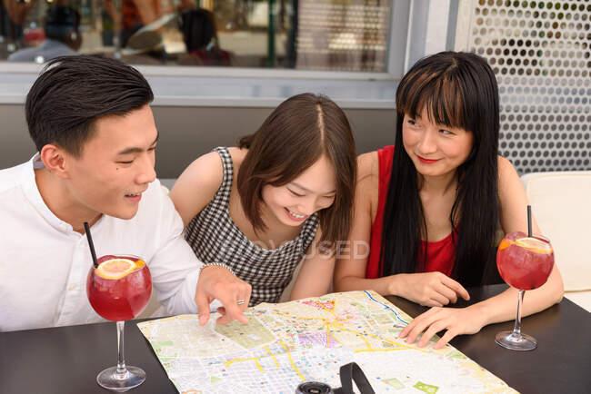 Tres personas asiáticas sonriendo y leyendo el mapa de la ciudad mientras están sentados en la mesa del café juntos - foto de stock