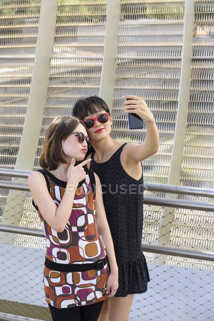 Asian women taking selfie near fence — Stock Photo