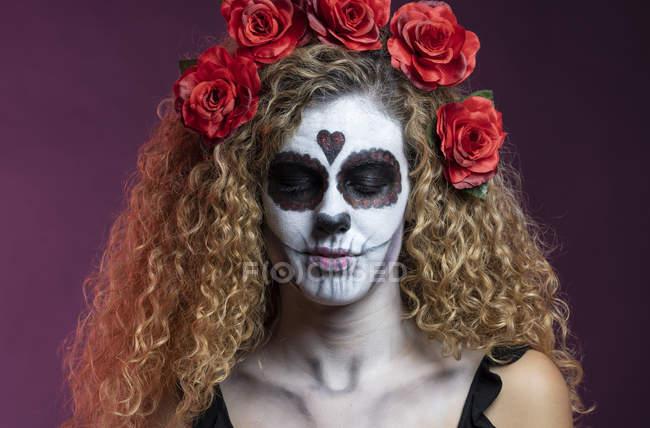 Giovane donna in tradizionale teschio di zucchero di Halloween compongono con ghirlanda di rose su sfondo nero . — Foto stock
