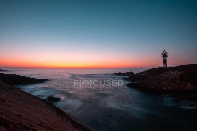 Перегляд маяк на узбережжі біля моря протягом величний sunset безхмарне вечір, Астурія, Іспанія — стокове фото