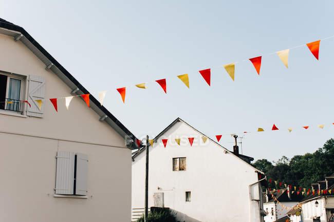 Барвисті трикутник прапори висить серед lovely приміські котеджів проти зніміть Синє небо — стокове фото