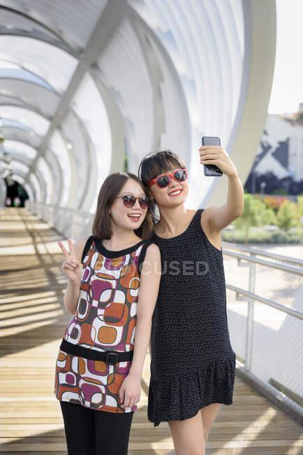 Азиатские женщины делают селфи возле забора — стоковое фото