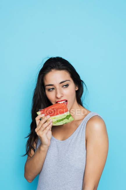 Чувственная брюнетка в сером телесном костюме ест свежий арбуз и смотрит в сторону на голубом фоне — стоковое фото
