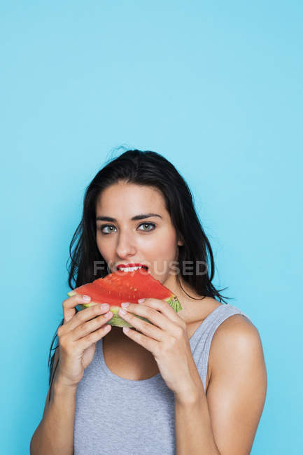 Portrait of young woman eating watermelon on blue background — Stock Photo