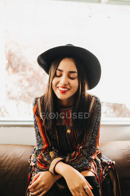 Attractive young lady in stylish outfit smiling and keeping eyes closed while sitting on back of soft sofa near window — Stock Photo