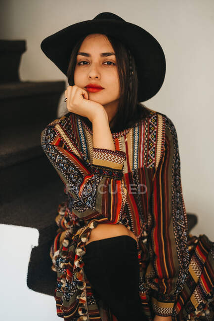 Beautiful young lady in stylish hat and dress supporting head and looking at camera while sitting on stairs at home — Stock Photo