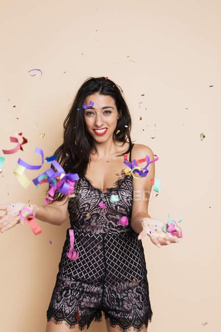 Ritratto di giovane donna felice in abito festivo con stelle filanti — Foto stock