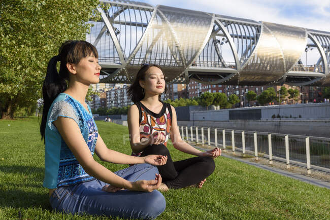 Asian women meditating in park — Stock Photo