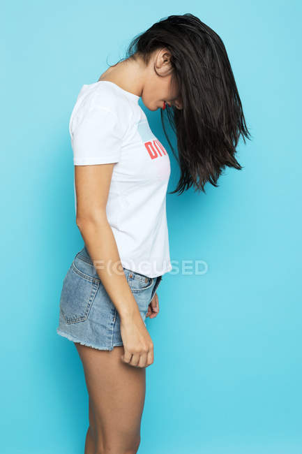 Brunette woman in white shirt and denim shorts with hair covering face standing on blue background — Stock Photo