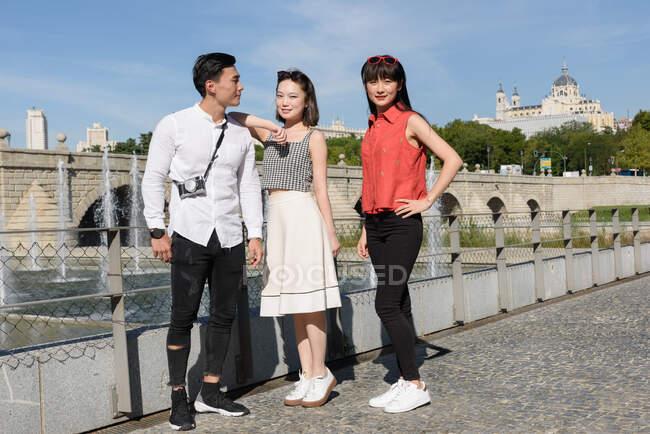 Азійські чоловіки і жінки в стильному одязі посміхаються і дивляться на камеру, стоячи біля паркану і фонтану в прекрасному парку. — стокове фото