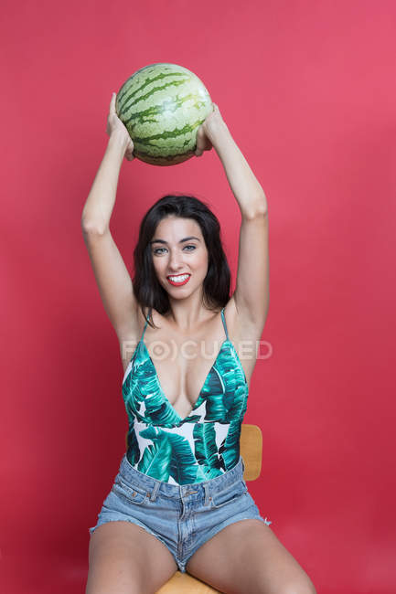 Young woman in denim shorts and top holding watermelon above head — Stock Photo